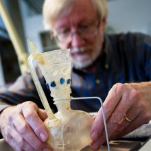A man holds a small glass pitcher with handle that has been cracked and repaired