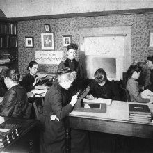 Black & white photo of eight women in an office doing research circa 1890.