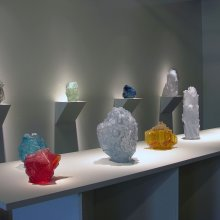 Multiple cast glass sculptures mounted on a grey wall