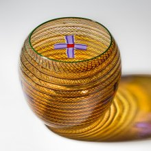 Translucent amber vase with a small purple and red cross on one side