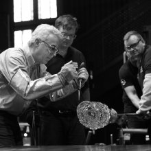 Mark Matthews works on a piece of glass on a punty held by another gaffer.