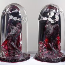 Cast glass sculpture of Red Ravens under cloches