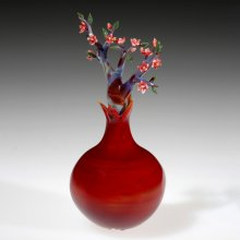 Red flower vase containing glass dogwood flowers
