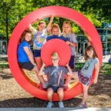 Five children pose in the Museum's hot spot sculpture, which is a larger red circle with a red dot in the center