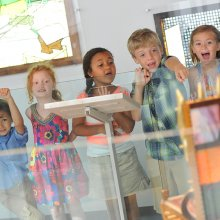 Kids in the gallery looking at glass art