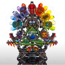 Glass sculpture featuring a human figure wearing a colorful headdress and holding a globe sits cross-legged on a multi-colored, two-headed turtle