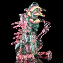 Green and pink glass sculpture of a monster with two rows of teeth