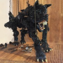 Black glass marionette monster with large teeth and claws